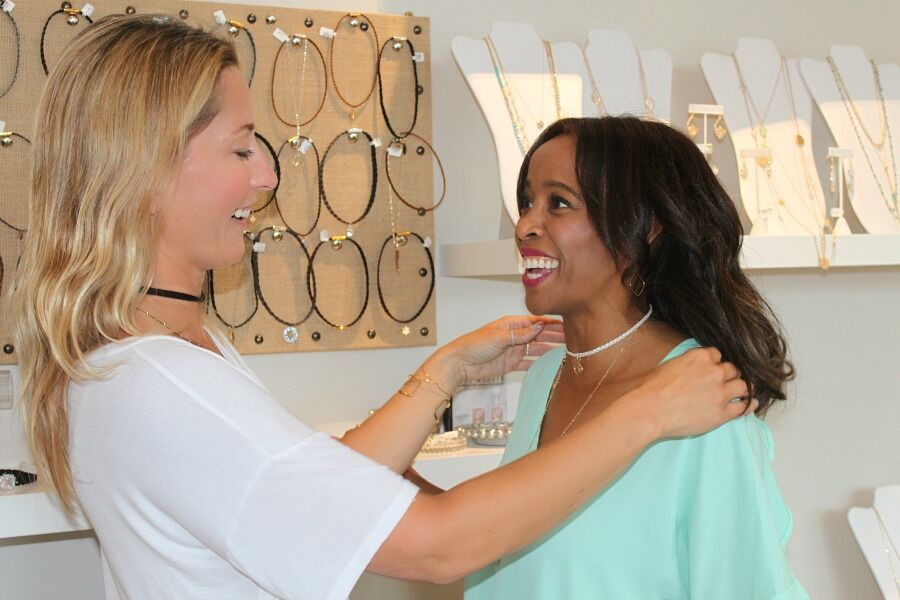 woman helping another woman put on AC4 Choker for Summer Accessory Trends