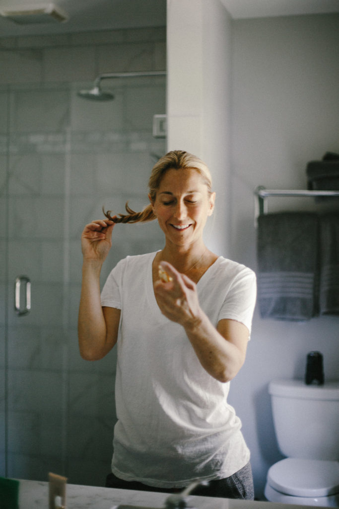 woman spraying beauty product on her face