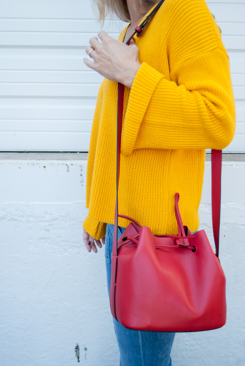 marigold sweater and a red bag