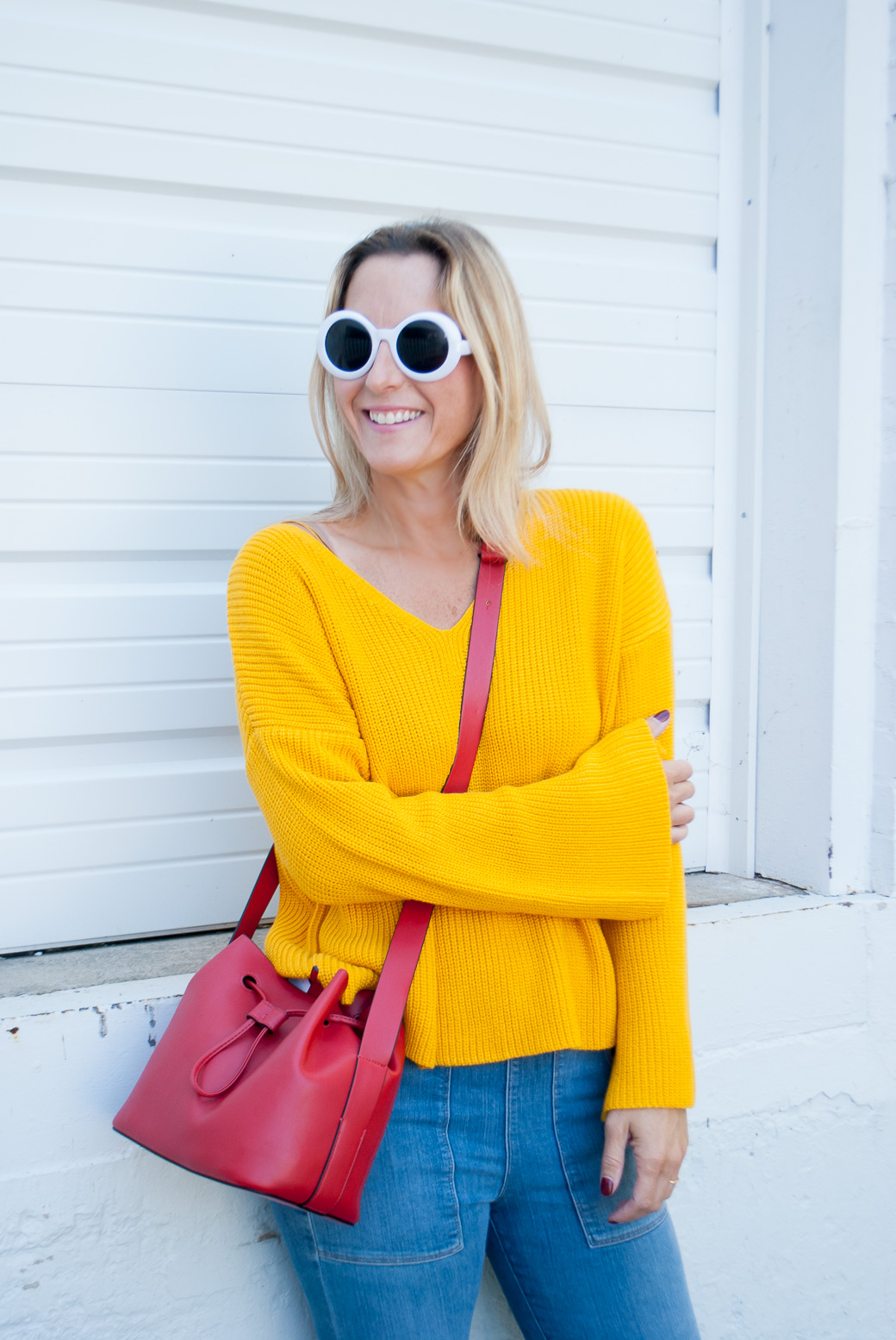 a woman wearing marigold fall color sweater and white sunnies and jeans