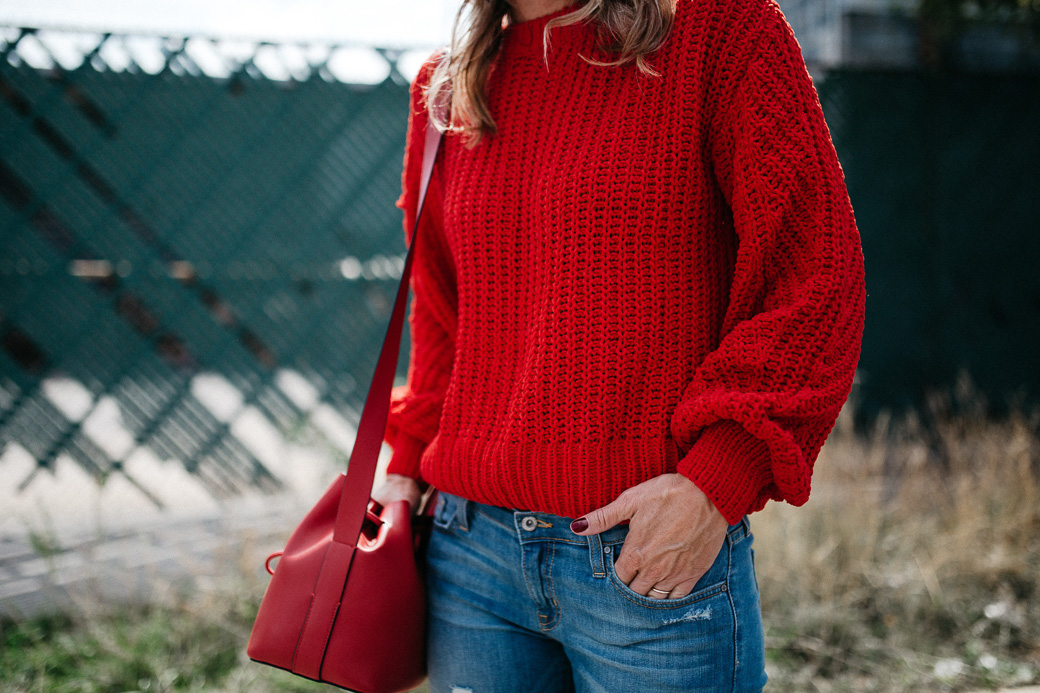 a red sweater and a red purse that you need for fall, along with blue jeans, 5 Sweaters Needed For Fall