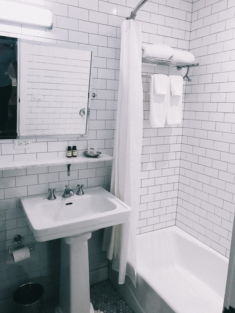 White tiled bathroom at Hotel HGU in NYC