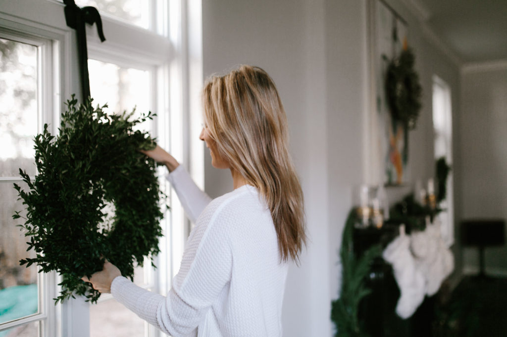 Hanging wreaths on window as a way to upgrade your holiday decor