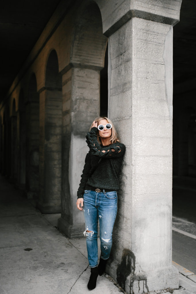 woman leaning on a wall and wearing go sweater night and jeans