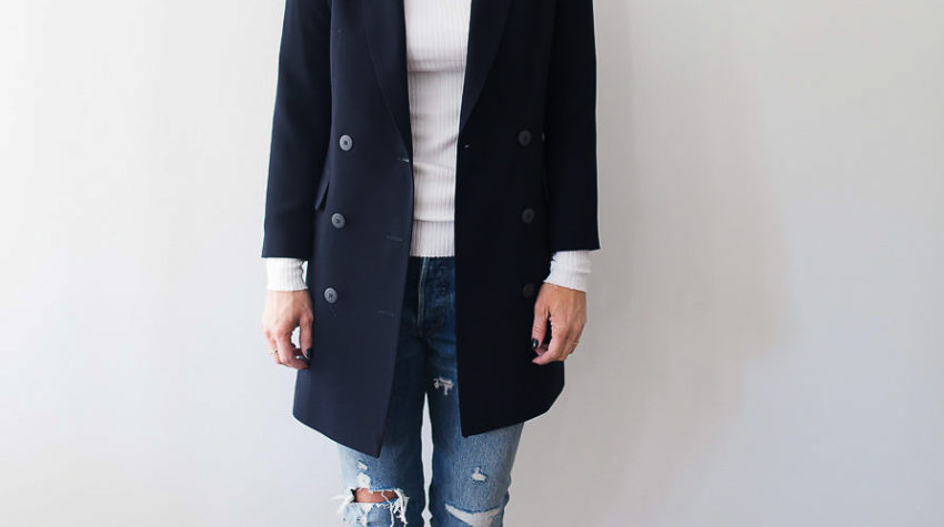 A pair of reto sneakers completes the look of a longer version navy blazer with a white top and distressed denim