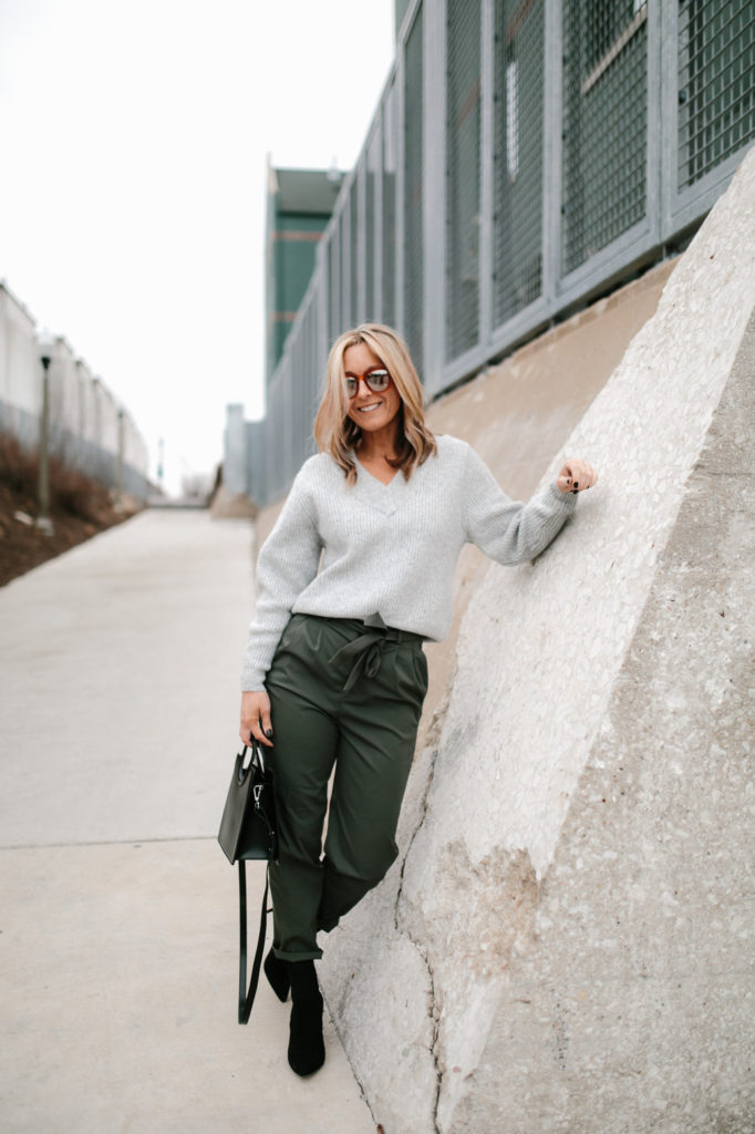 Paper bag pant in olive green with grey chunky knit sweater, black sock booties and a black structured bag