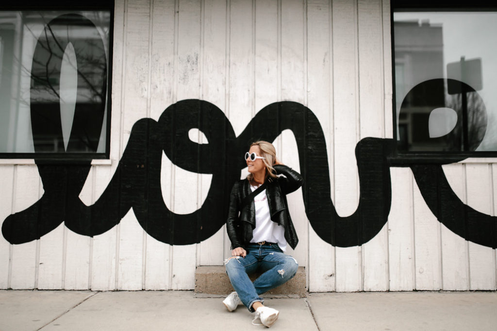 Love mural background dressed in denim, white logo tee, sneakers and leather jacket