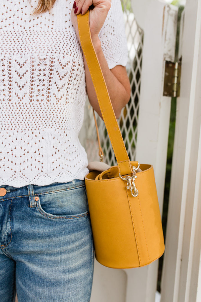 White eyelet top with marigold bucket style bag