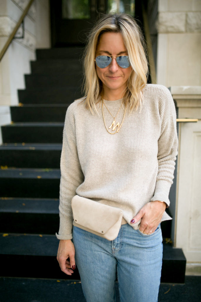 Cashmere sweater with suede belt bag and denim