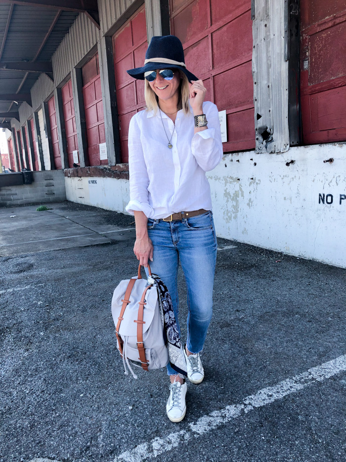 Megan Medica is wearing a white button-down, jeans and sneakers