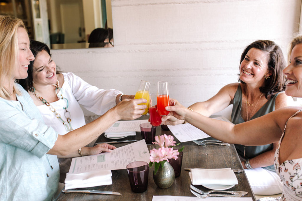 cheers to brunch and friends with four women and colorful mimosa drinks