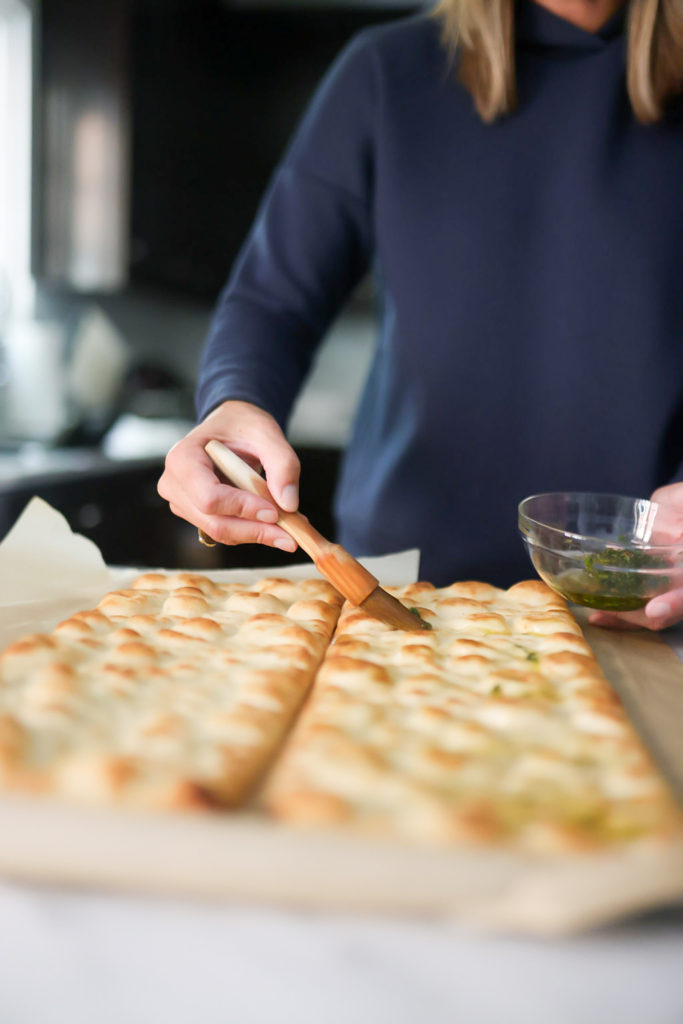 person brushing olive oil on flatbreads