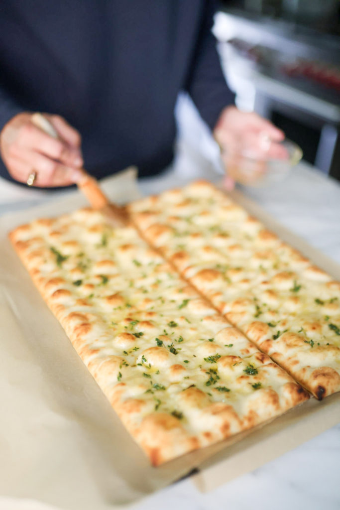 woman adding olive oil on top of a flatbreads