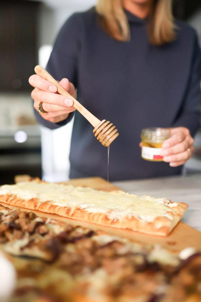 person adding honey on flatbreads
